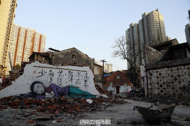 "The words on the wall are from a Tang dynasty poem that reads, ""Last night l heard a sound of wind and rain. How many blossoms have fallen again.""(Weibo/nanfangdushibao) source: http://qz.com/333147/this-poetic-street-art-paying-homage-to-old-shanghai-is-being-erased-by-government-bureaucrats/"